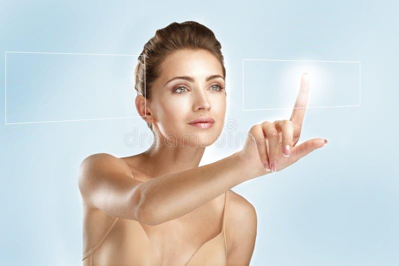 Jeune beau modèle touchant un panneau futuriste d'écran photo libre de droits