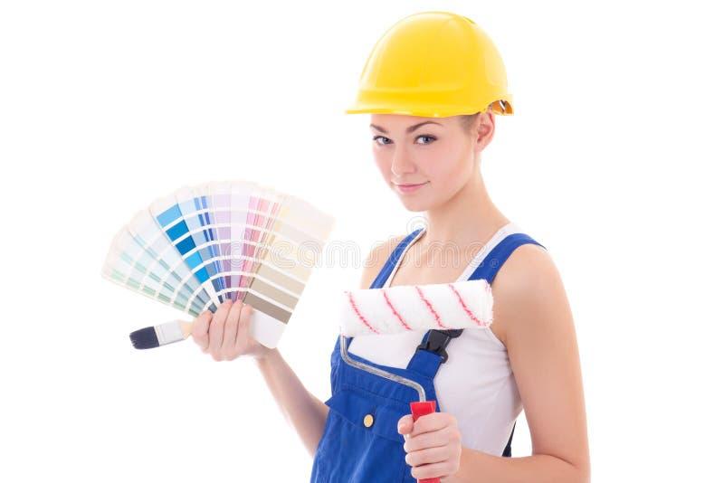 Jeune beau peintre de femme dans les vêtements de travail avec le pinceau et la Co photographie stock