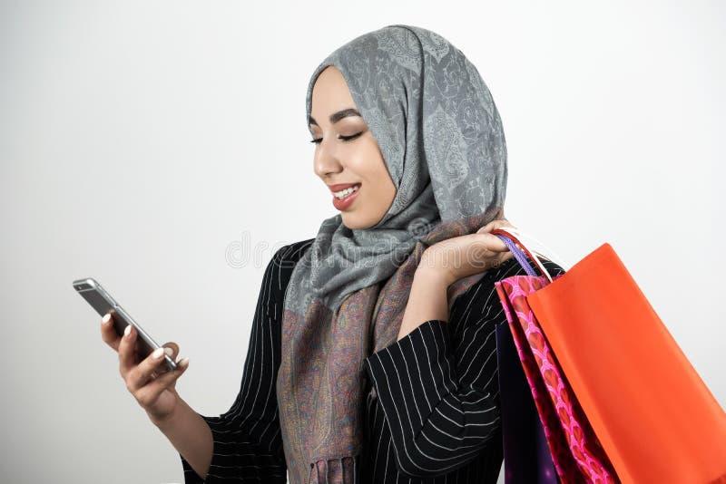 Jeune beau smartphone de tapement de port musulman de sourire de foulard de hijab de turban de femme d'affaires avec une main et photographie stock libre de droits