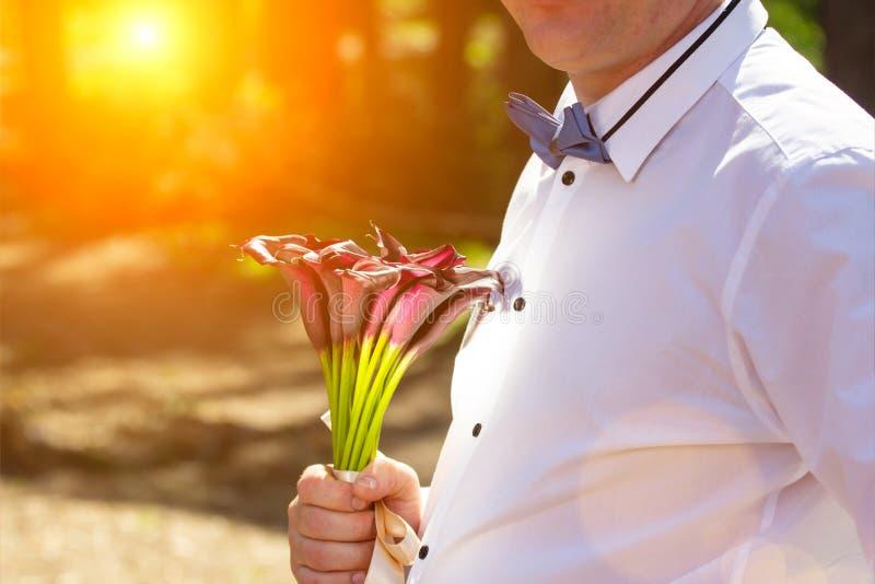 Jeune beau stule occasionnel enamouré attrayant headsome d'homme avec des fleurs au coucher du soleil Copiez l'espace images libres de droits
