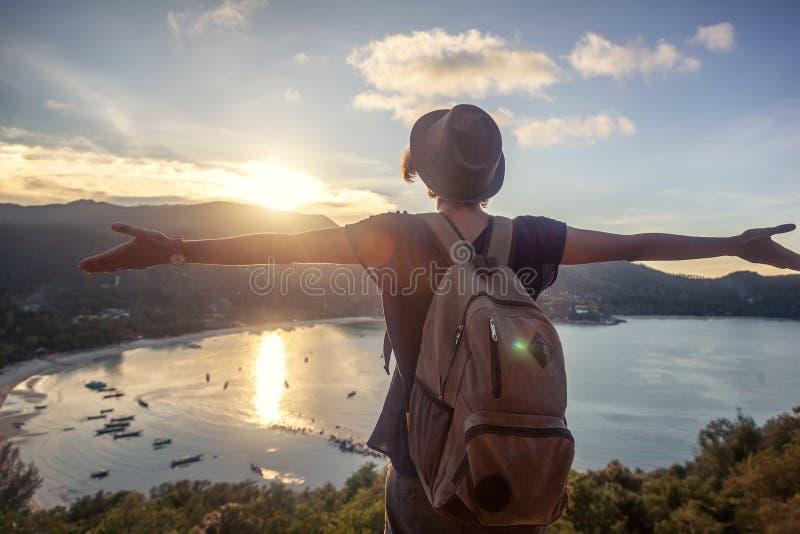Jeune beau voyageur de hippie de femme regardant le coucher du soleil et le bea photographie stock