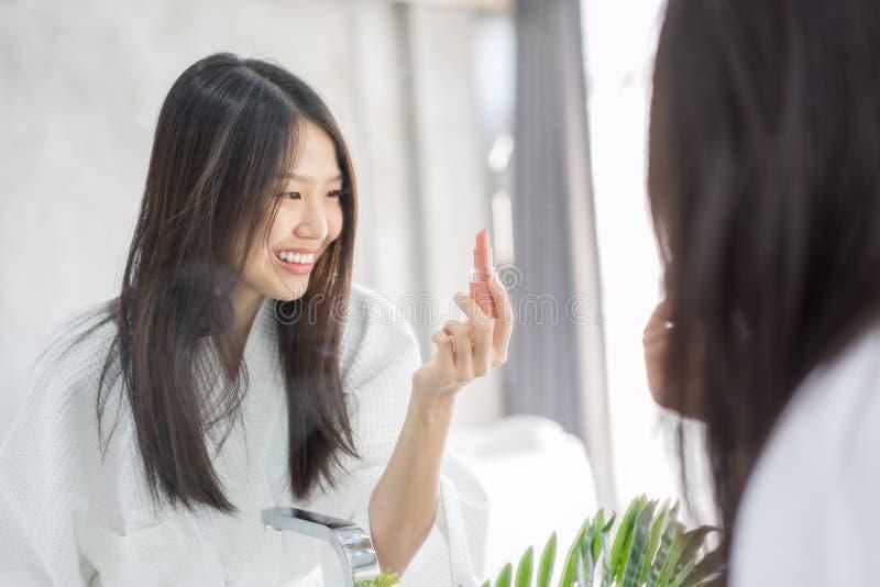 Jeune beauté femelle asiatique de maquillage par le rouge à lèvres photographie stock