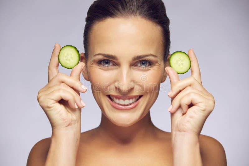 Jeune beauté souriant avec des tranches de concombre photo stock