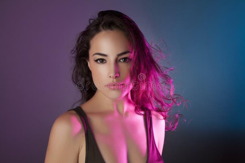 Jeune beauté sous les lumières colorées photographie stock libre de droits