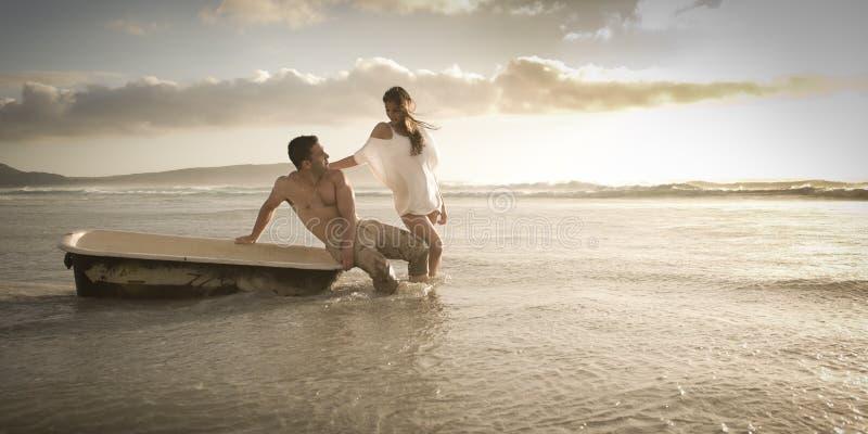 Jeune bel après-midi de dépense de couples sur la plage avec la vieille baignoire image libre de droits