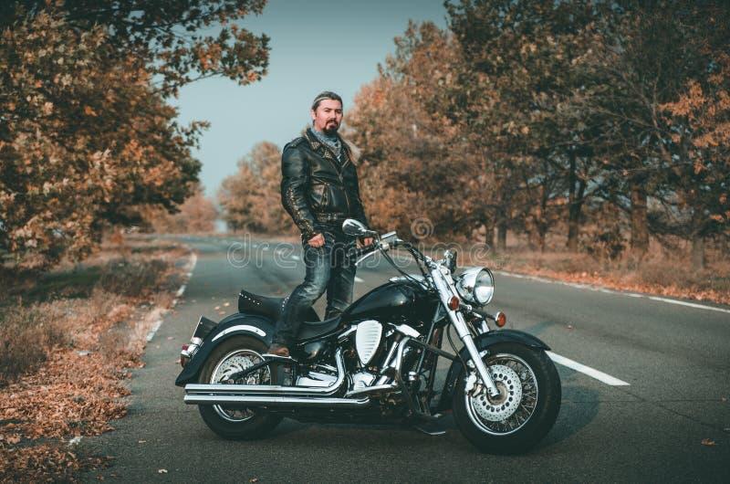 Jeune bel homme caucasien posant avec la moto photos stock