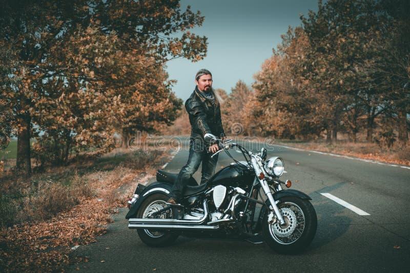 Jeune bel homme caucasien posant avec la moto photo stock