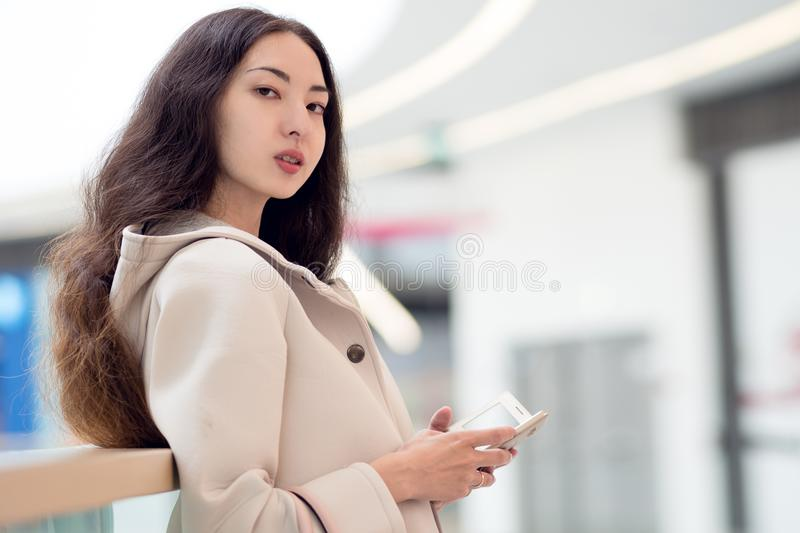 Jeune belle Asiatique de fille, utilisations téléphone portable, fond, centre commercial ou centre d'affaires image libre de droits