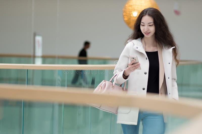 Jeune belle Asiatique de fille, utilisations téléphone portable, fond, centre commercial ou centre d'affaires images libres de droits