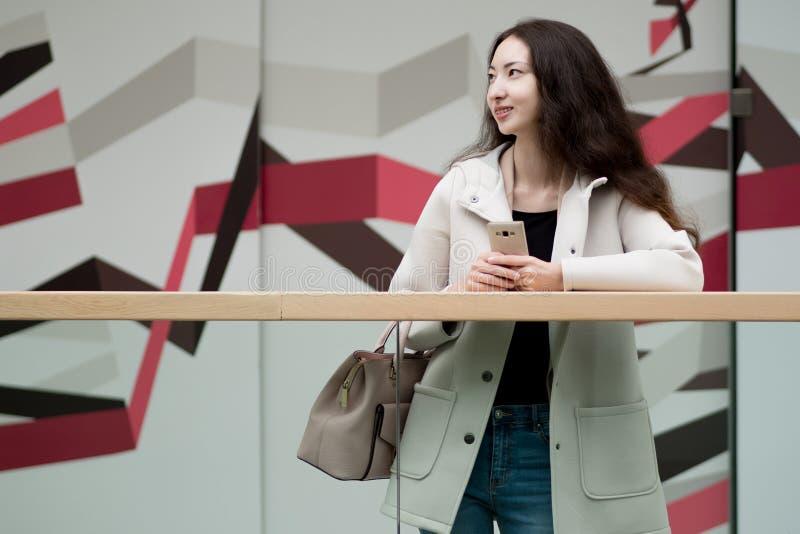 Jeune belle Asiatique de fille, utilisations téléphone portable, fond, centre commercial ou centre d'affaires image stock