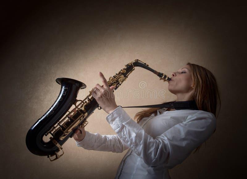 Jeune belle blonde aux cheveux longs avec le saxophone images libres de droits