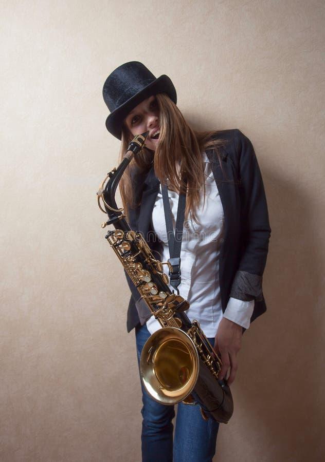 Jeune belle blonde aux cheveux longs avec le saxophone photos libres de droits