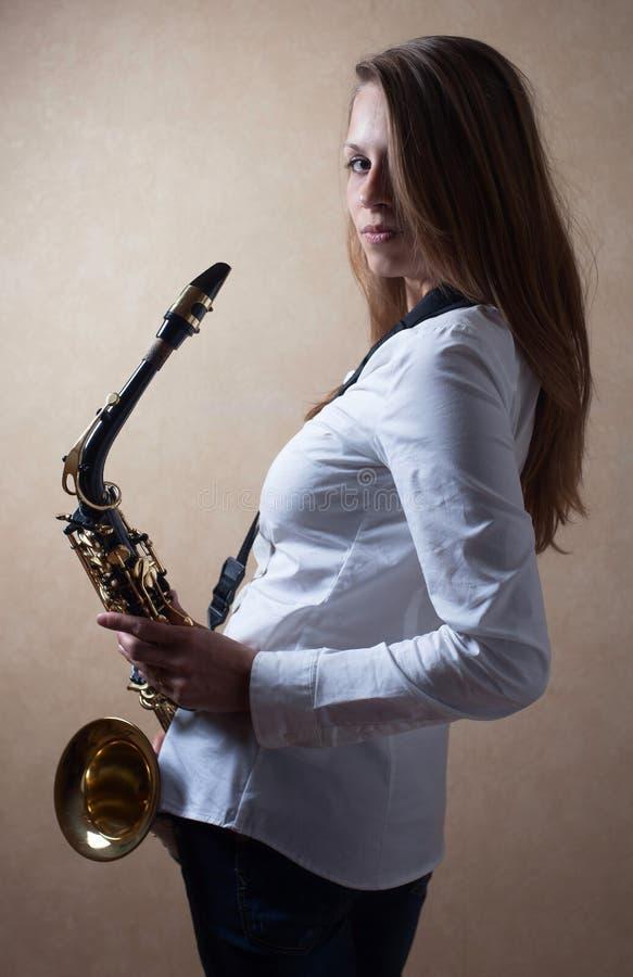Jeune belle blonde aux cheveux longs avec le saxophone photographie stock libre de droits