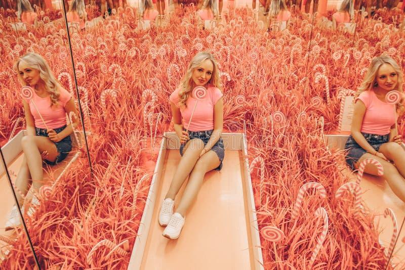Jeune belle blonde dans un chemisier rose sur le fond rose mou avec la lucette rose lumineuse multicolore image stock