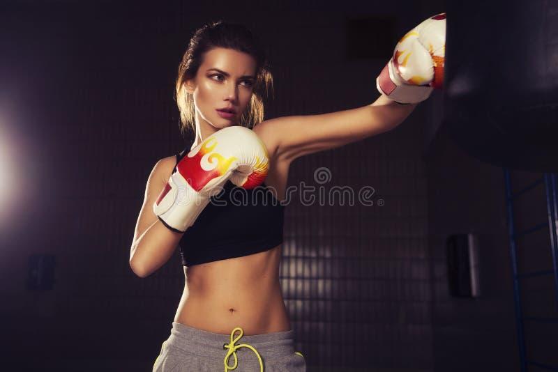 Jeune belle boxe mince convenable de femme de brune dans les vêtements de sport Le DA photographie stock libre de droits