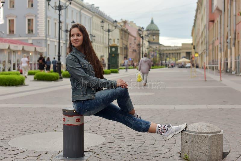 Jeune belle brune dans un costume de denim sur la rue photos libres de droits