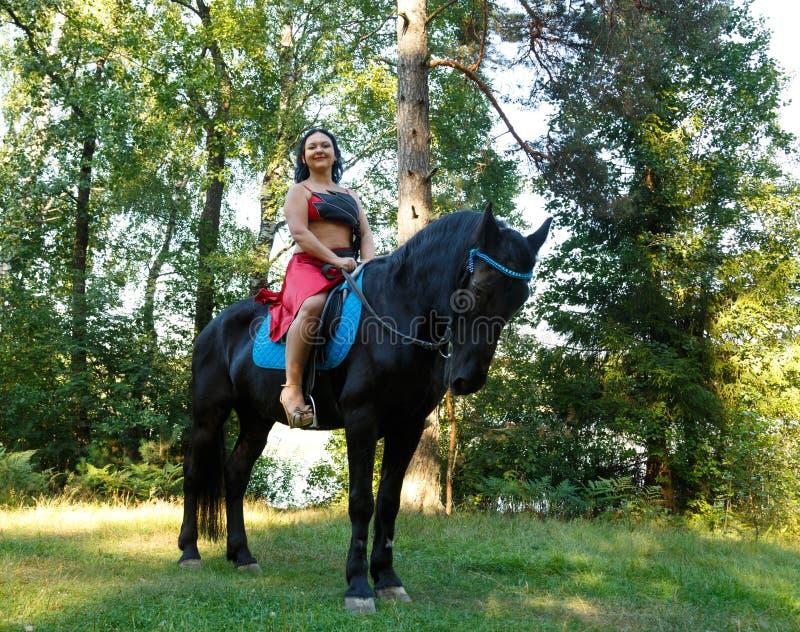 Jeune belle brune dans un costume rouge dans une selle sur un cheval dans le plan global de forêt images libres de droits