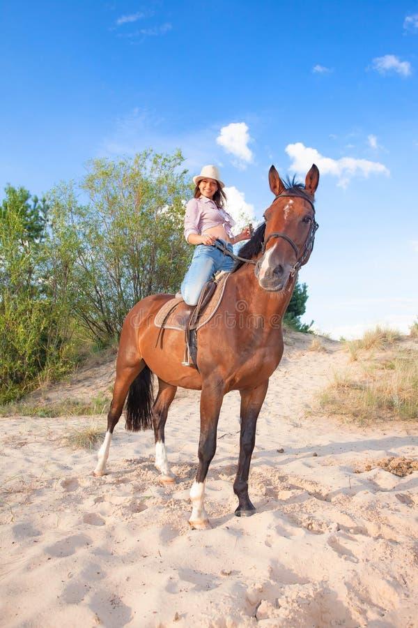Jeune belle cow-girl avec un cheval dans les dunes photographie stock libre de droits