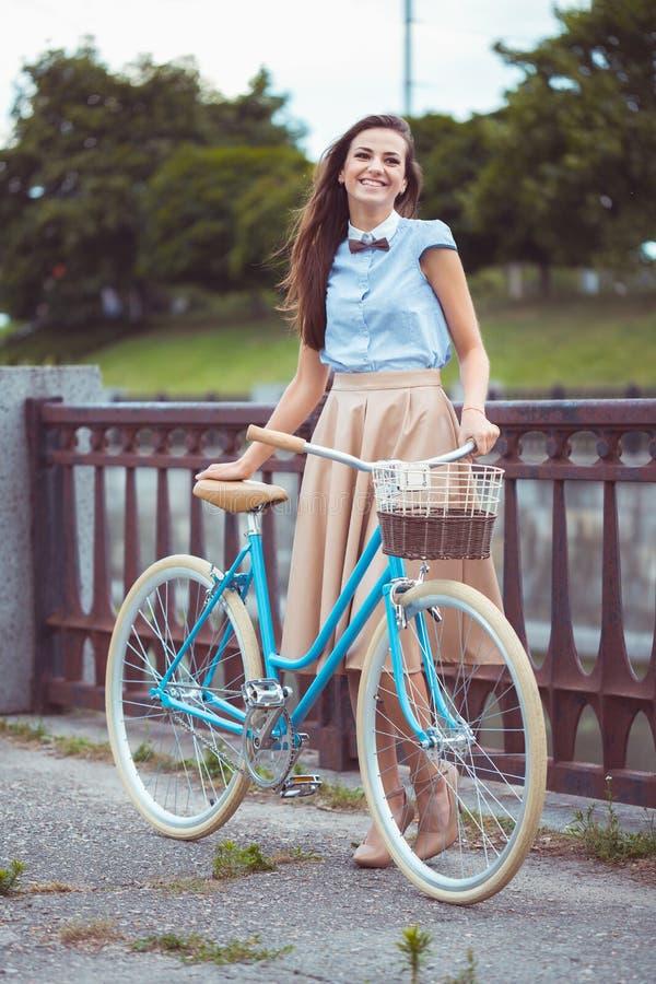 Jeune belle, d'une manière élégante habillée femme avec la bicyclette photographie stock libre de droits