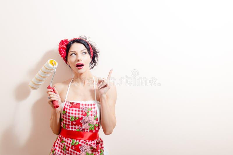 Jeune belle dame de brune dans l'amusement tenant le traversin de peinture et ayant refourbir l'idée se dirigeant avec le doigt r photo libre de droits