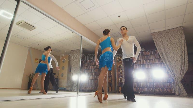 Jeune belle danse d'homme et de femme et danse latine de pratique dans des costumes dans le studio photos stock
