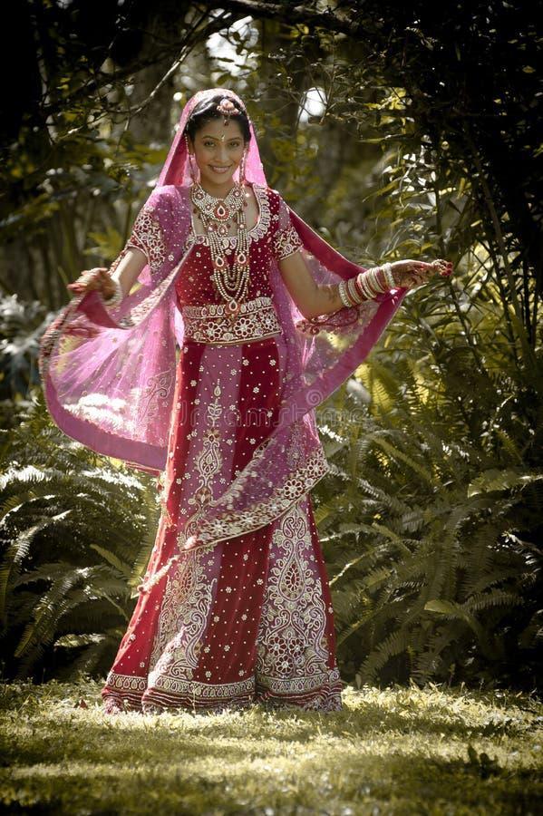 Jeune belle danse indoue indienne de jeune mariée sous l'arbre photographie stock libre de droits