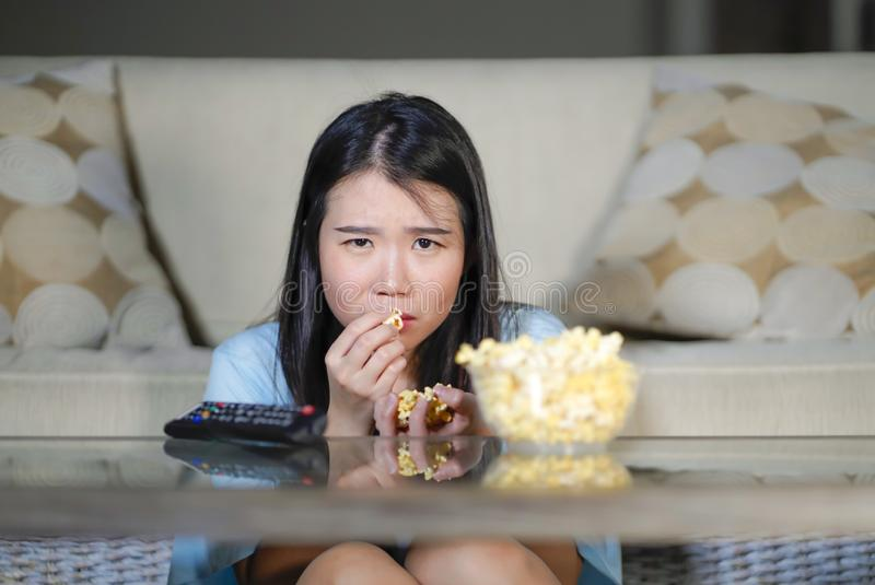 Jeune belle et décontractée femme japonaise asiatique observant le drame coréen à la télévision sur le film romantique triste man image stock