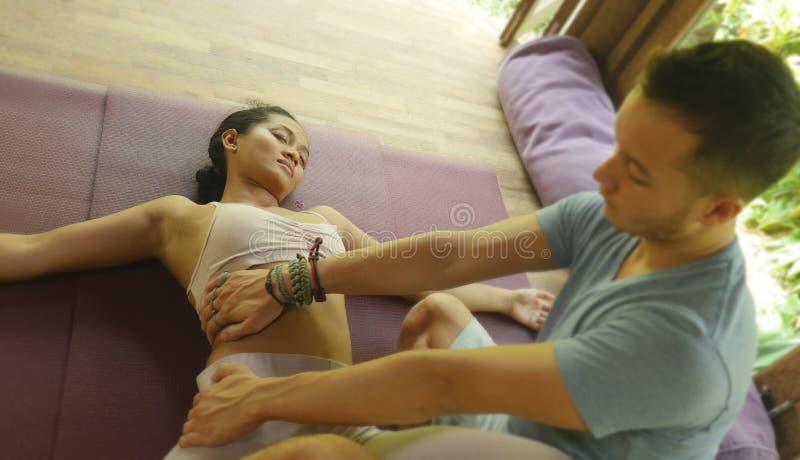 Jeune belle et exotique femme asiatique de Balinese se trouvant sur le tapis de studio recevant le massage tha?landais traditionn images stock
