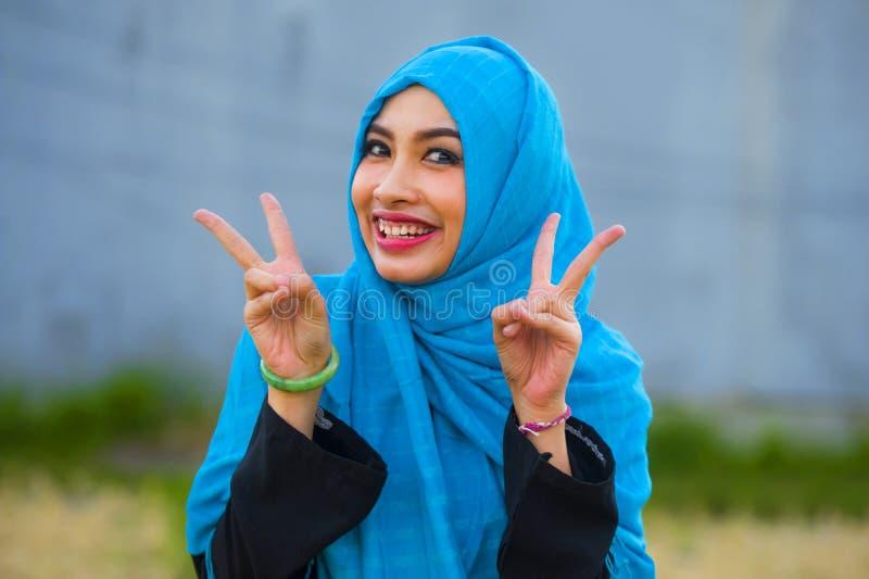 Jeune belle et heureuse femme asiatique dans l'écharpe principale musulmane de hijab posant à l'appareil-photo espiègle ayant l'a photo libre de droits