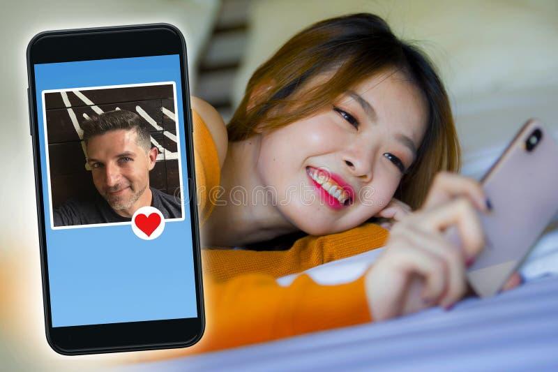 Jeune belle et heureuse femme coréenne asiatique dans le lit utilisant le téléphone portable ayant l'appel visuel ou flirtant en  image libre de droits