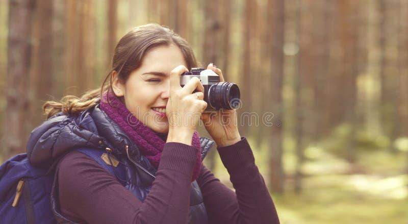 Jeune, belle et heureuse femme marchant dans la forêt et prenant pi photo stock