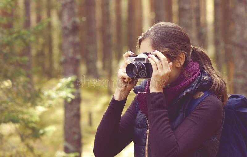 Jeune, belle et heureuse femme marchant dans la forêt et prenant pi photographie stock