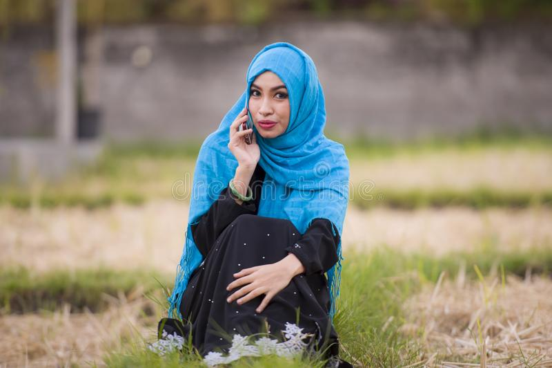 Jeune belle et heureuse femme musulmane portant l'écharpe islamique de tête de hijab et l'habillement traditionnel parlant au tél photo stock