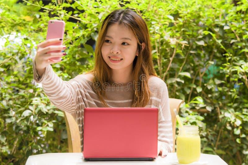 Jeune belle et heureuse fille chinoise asiatique d'étudiant s'asseyant au jardin de café fonctionnant avec l'ordinateur portable  photo stock