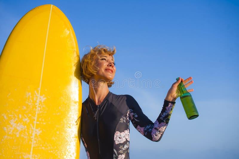 Jeune belle et heureuse fille sexy de surfer tenant la bouteille à bière potable gaie de sourire jaune de panneau de ressac appré images stock