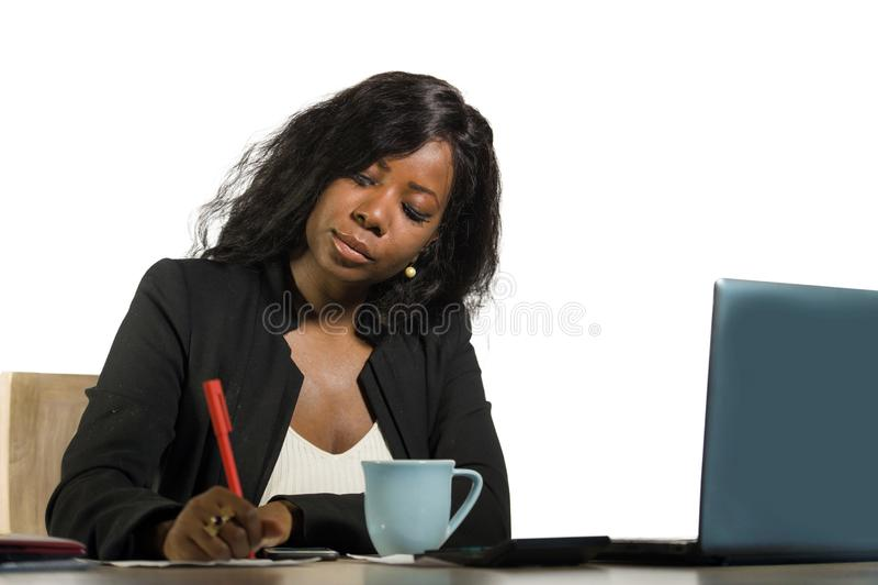 Jeune belle et occupée femme d'affaires afro-américaine noire écrivant des notes sur le fonctionnement de bureau avec l'ordinateu photos stock