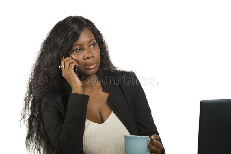 Jeune belle et occupée femme d'affaires afro-américaine noire parlant au téléphone portable au bureau fonctionnant avec le boire  photographie stock libre de droits