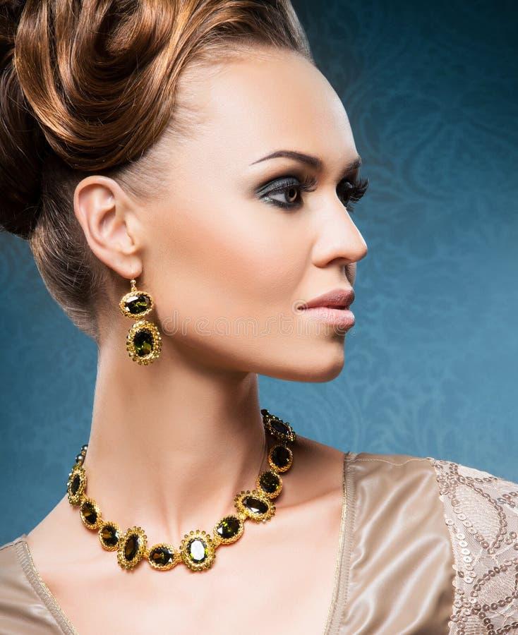 Jeune, belle et riche femme en bijoux d'or et des pierres photos stock