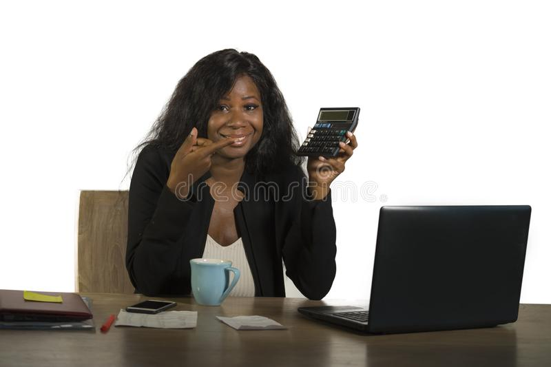 Jeune belle et sûre femme d'affaires afro-américaine noire travaillant au bureau d'ordinateur de bureau souriant tenant la calcul photo libre de droits