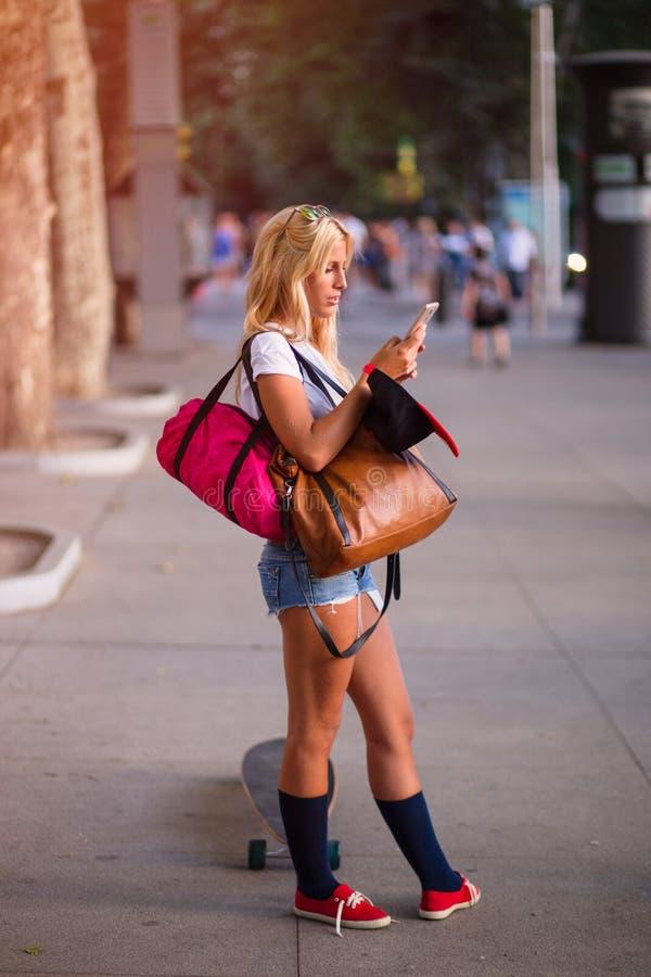 Jeune belle femme à l'aide de son téléphone photo stock