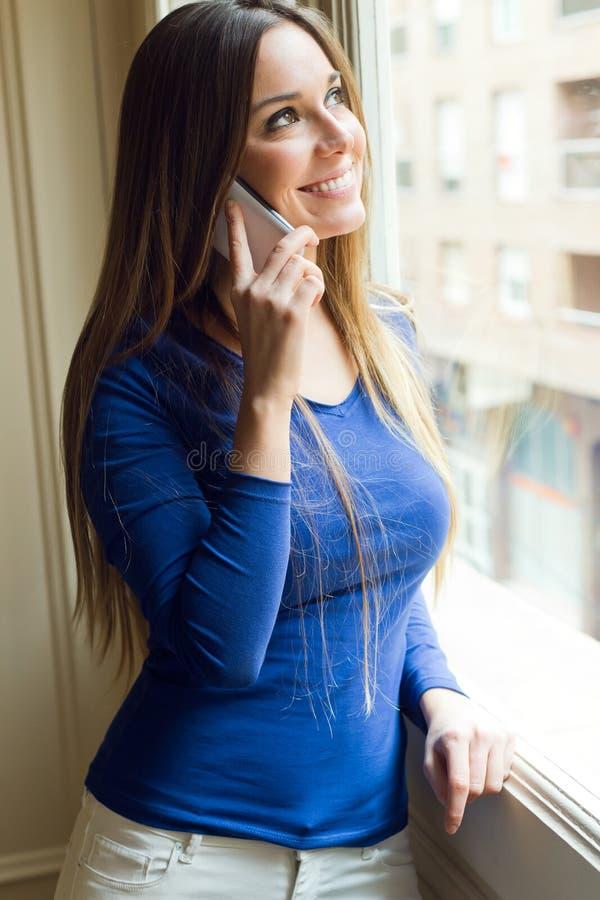 Jeune belle femme à l'aide de son téléphone portable à la maison images libres de droits