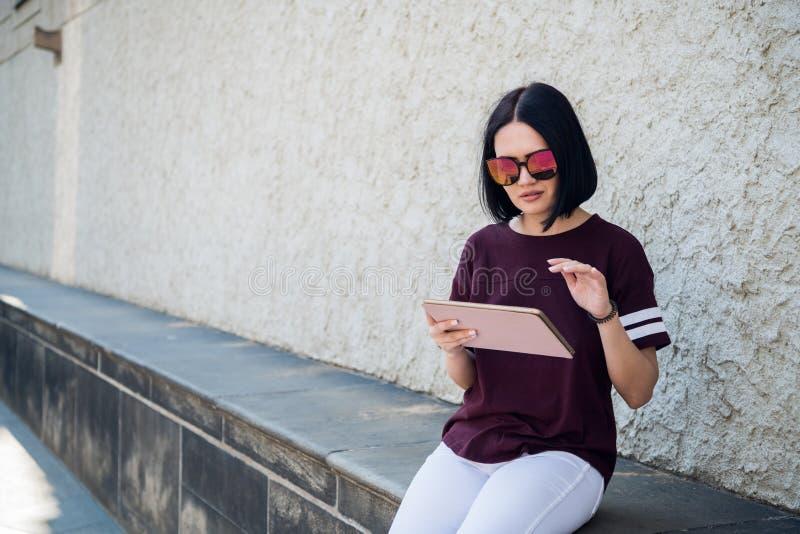 Jeune belle femme à l'aide du comprimé numérique appréciant le matin ensoleillé dans la ville, Internet de lecture rapide photos stock