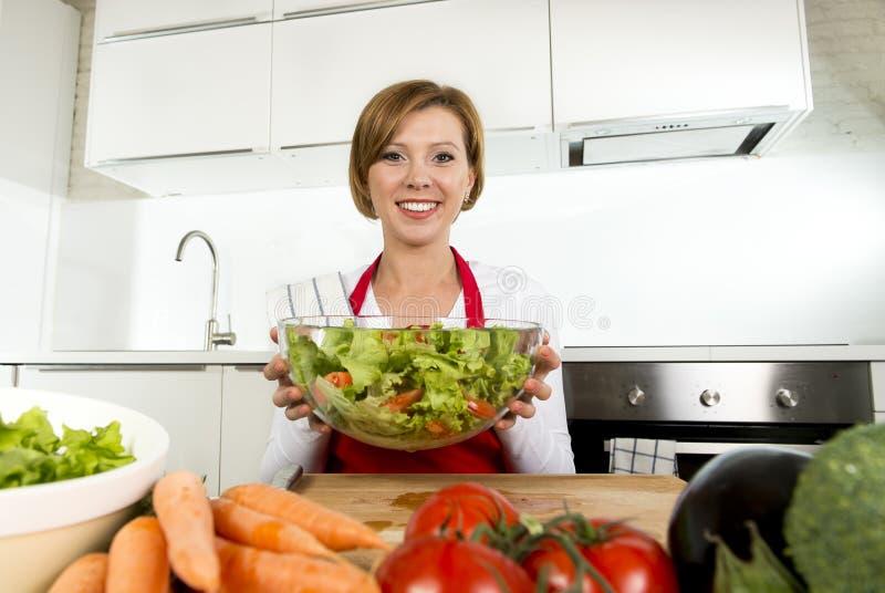 Jeune belle femme à la maison de cuisinier à la cuisine moderne préparant le sourire végétal de saladier heureux photos stock