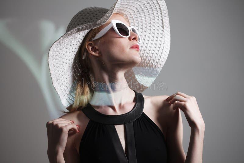 Jeune belle femme à la mode avec le maquillage à la mode Appareil-photo de regard modèle, lunettes élégantes de port, chapeau La  images stock