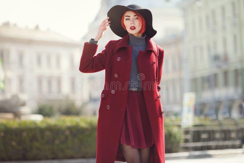 Jeune belle femme à la mode posant sur la rue Chapeau à large bord noir élégant de port modèle, manteau rouge Fille photos libres de droits