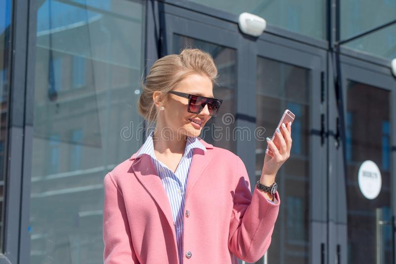 Jeune belle femme élégante dans le manteau rose marchant dans la rue photo stock