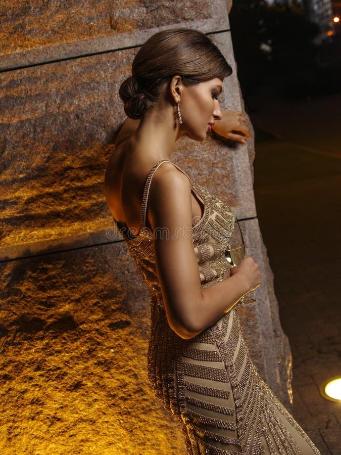 Jeune belle femme élégante vivement habillée avec le maquillage et la coiffure dans la robe de scintillement égalisante expressiv image libre de droits