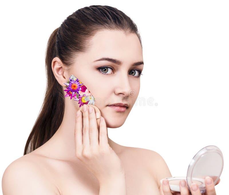 Jeune belle femme appliquant des fleurs cosmétiques sur le visage photos stock