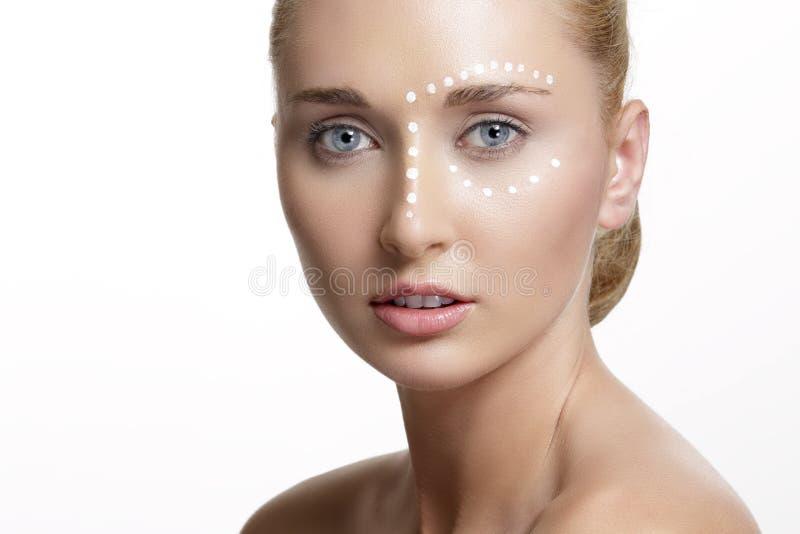 Jeune belle femme appliquant la crème sur sa peau images libres de droits