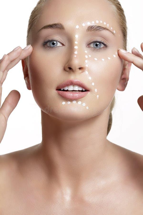 Jeune belle femme appliquant la crème sur sa peau photographie stock